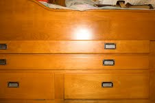 map drawers with berth above, settee below. Beautiful.